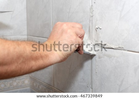 The male hand with the rubber spatula applies grout on a seam between tiles in a bathroom. Home repairs. #467339849