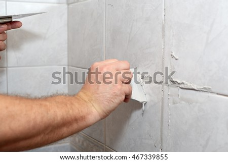 The male hand with the rubber spatula applies grout on a seam between tiles in a bathroom. Home repairs. #467339855