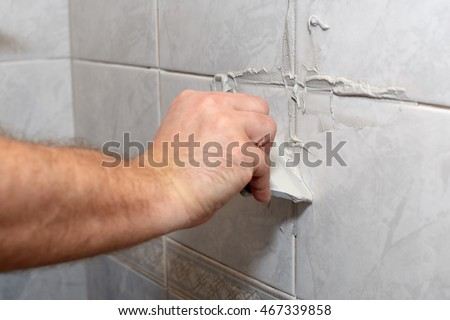 The male hand with the rubber spatula applies grout on a seam between tiles in a bathroom. Home repairs. #467339858
