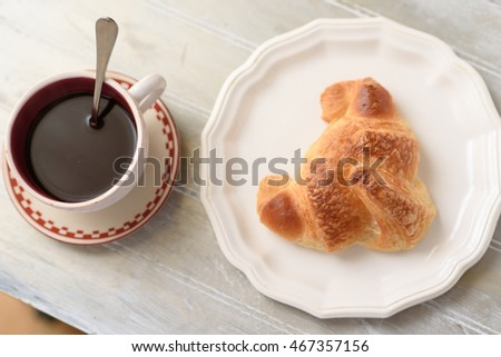 Selective focus on croissant brown skin. A fresh croissant on the white plate beside a cup of coffee on the wooden table. #467357156