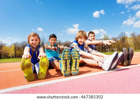 Happy kids doing stretching exercises on a stadium #467385302