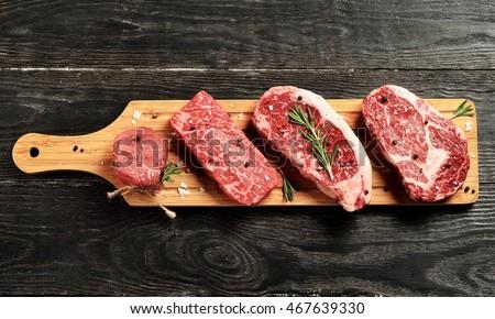 Fresh raw Prime Black Angus beef steaks on wooden board: Tenderloin, Denver Cut, Striploin, Rib Eye Royalty-Free Stock Photo #467639330