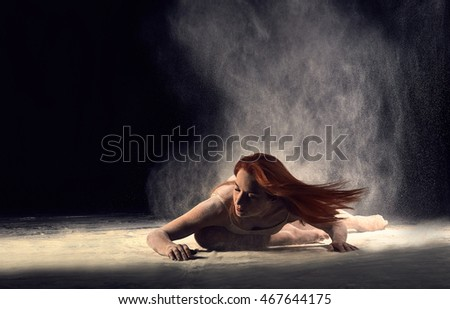 Woman dancer lying on the floor in a ballet pose with flour. Redheaded woman ballerina posing in beige bathing suit on a black background. #467644175