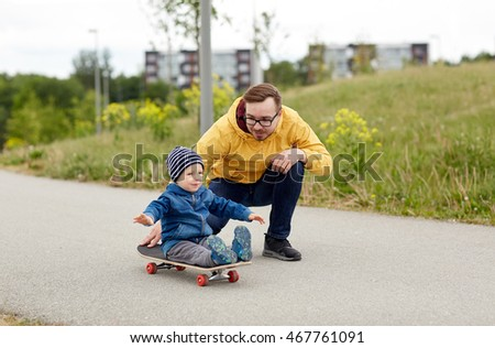 family, childhood, fatherhood, leisure and people concept - happy father and little son riding on skateboard #467761091
