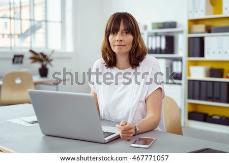 Middle-aged businesswoman working at a laptop computer at her desk in the office pausing to look thoughtfully at the camera #467771057