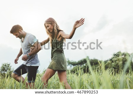 Outdoor shot of young couple walking through meadow hand in hand. Man and woman talking walk through grass field in countryside. #467890253