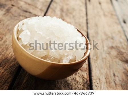 White sea salt in brown bowl on dark wooden texture background in still life style #467966939