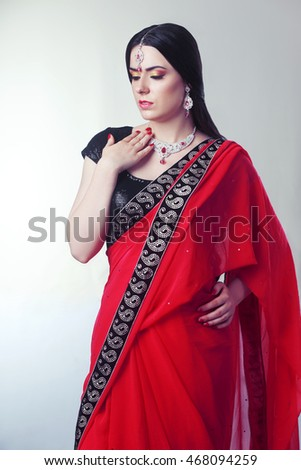 portrait of indian woman greeting somebody in red sari isolated on white background in photostudio #468094259