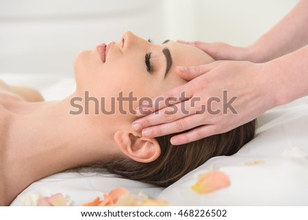 Carefree young woman getting treatment at beauty salon #468226502