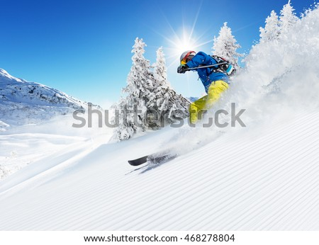 Skier on piste running downhill in beautiful Alpine landscape. Blue sky on background. Free space for text #468278804