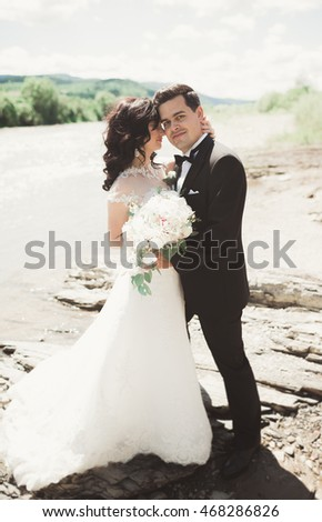 Elegant stylish happy brunette bride and gorgeous groom on the background of a beautiful waterfall in the mountains #468286826