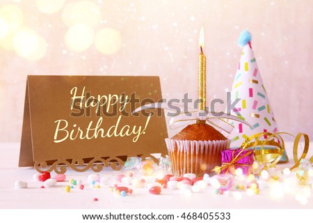 Birthday concept with cupcake and candle next to greeting card on wooden table. Glitter lights overlay. Selective focus
