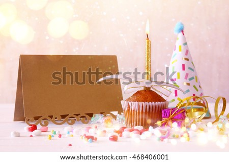 Birthday concept with cupcake and candle next to empty greeting card on wooden table. Glitter lights overlay. Selective focus