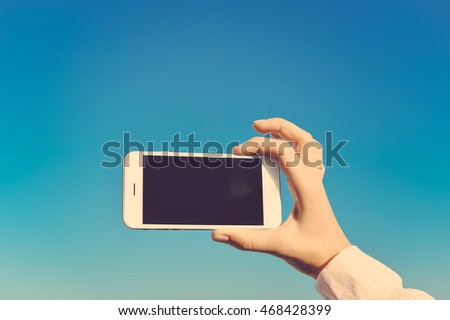 Female hand taking photo of the sky using smartphone, sunny outdoors background
