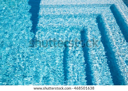 Swimming pool steps in the morning sunlight with shadows accentuating their pleasant curved shapes. The steps are tiles with tiles of various shades of blue. #468501638