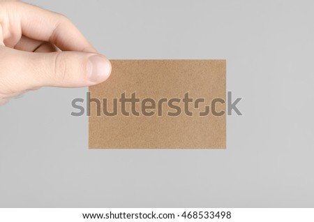Kraft Business Card Mock-Up (85x55mm) - Male hands holding a kraft card on a gray background. #468533498