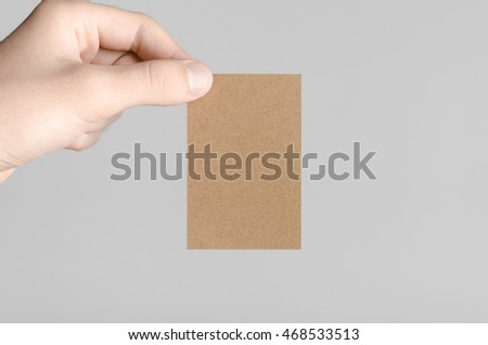 Kraft Business Card Mock-Up (85x55mm) - Male hands holding a kraft card on a gray background. #468533513