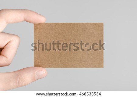 Kraft Business Card Mock-Up (85x55mm) - Male hands holding a kraft card on a gray background.