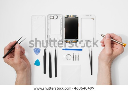 Repairman workplace with phone and special tools. Disassembled smartphone with disassembling instruments and repairer hands on white background. Electronics repair service, device production concept #468640499