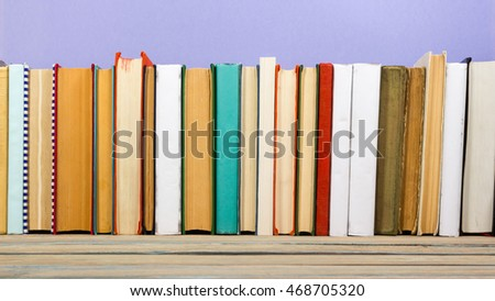 Books on grunge wooden table desk shelf in library. Back to school background with copy space for your ad text. Old hardback   no labels, blank spine #468705320