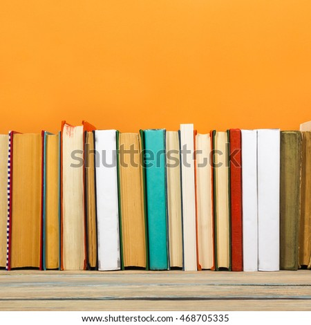 Books on grunge wooden table desk shelf in library. Back to school background with copy space for your ad text. Old hardback no labels, blank spine #468705335