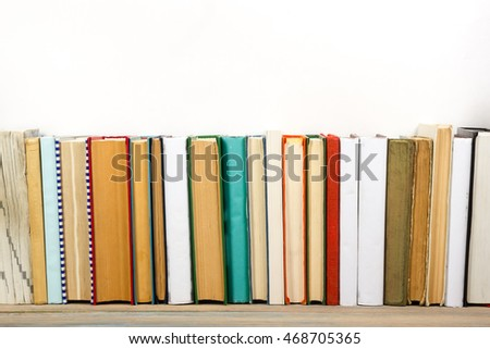 Books on grunge wooden table desk shelf in library. Back to school background with copy space for your ad text. Old hardback   no labels, blank spine #468705365
