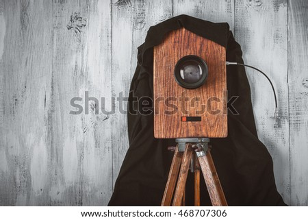 Old studio camera stands on a wooden tripod.Stylized photo