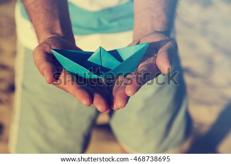Guy holding paper boat outdoors.   #468738695