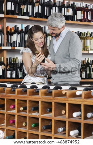 Couple With Wine Bottle Standing At Rack #468874952