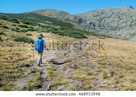 GREDOS, SPAIN - AUGUST 3, 2016: A kid walking up to the summit of the surrounding mountains in Gredos, Avila. #468953948
