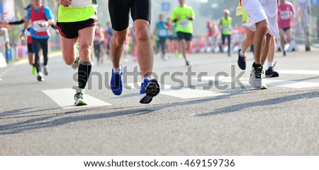 Unidentified marathon athletes legs running on city road #469159736