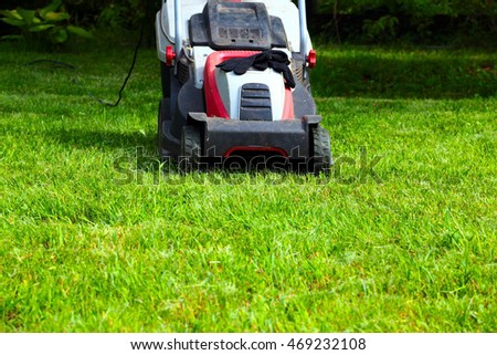 electric lawn mower and a beautiful lush grass #469232108