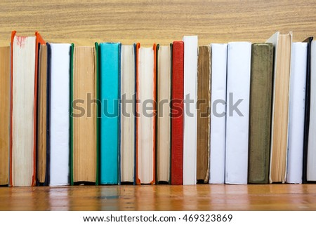 Books on grunge wooden table desk shelf in library. Back to school background with copy space for your ad text. Old hardback   no labels, blank spine #469323869