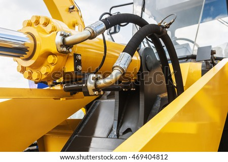hydraulics tractor yellow. focus on the hydraulic pipes Royalty-Free Stock Photo #469404812