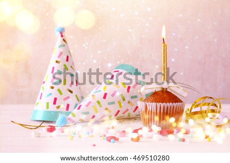 Birthday concept with cupcake and candle, party hat on wooden table. Glitter lights overlay. Selective focus #469510280