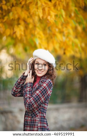 Happy autumn young woman in hat outdoors, smiling girl in French beret walking in park at sunset, soft film grain #469519991