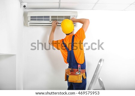 Technician repairing air conditioner on the wall #469575953