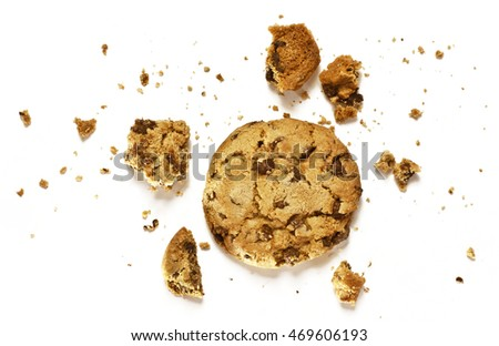 A photo of a crunchy chocolate chips cookie with crumbs around it, shot from above on a white background, with copyspace