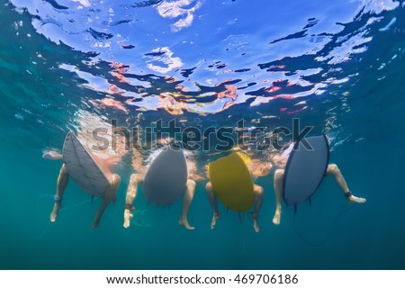 Young girls in bikini have fun - surfers sit on surf boards, wait for big ocean wave. Females feet underwater photo. People in water sport adventure camp, beach extreme swim on summer beach vacation
