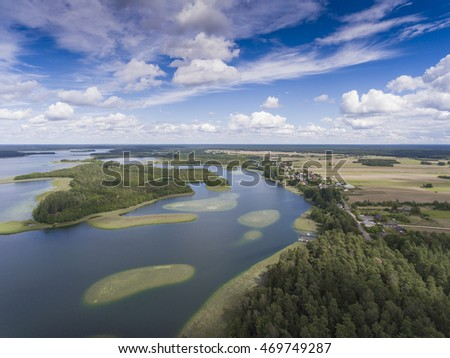 View of small islands on the lake in Masuria and Podlasie district, Poland. Blue water and whites clouds. Summer time. View from above. #469749287