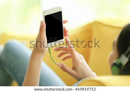 Woman listening to music on smartphone in the room #469819712