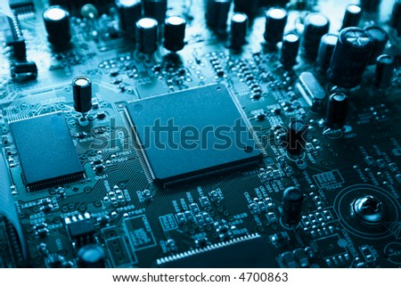 Big CPU surrounded by capacitors resistors and other components.Bright image in cyan-neon tone. #4700863