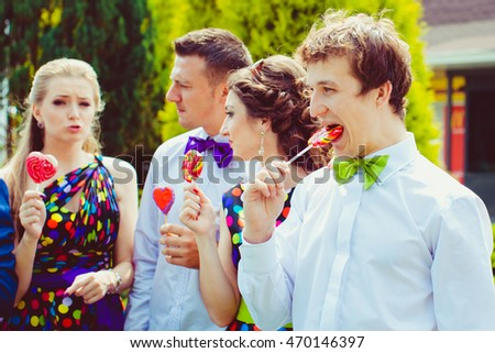 Groomsman in green bow tie puts a large sugar candy in his mouth #470146397