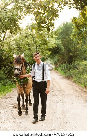 groom in forest with horses. Man with dark horse #470157512