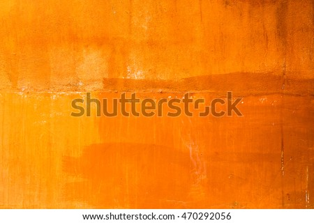 Rough concrete wall painted in orange with brush strokes