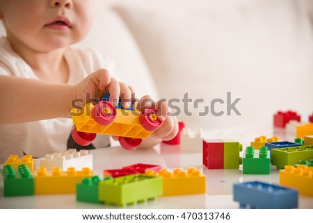Close up of child's hands playing with colorful plastic bricks at the table. Toddler having fun and building out of bright constructor bricks. Early learning.  stripe background. Developing toys #470313746