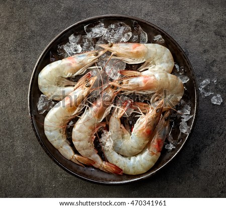 fresh raw prawns and ice on black plate, top view #470341961