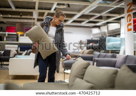 Pretty, young woman choosing the right furniture for her apartment in a modern home furnishings store (color toned image; shallow DOF) #470425712