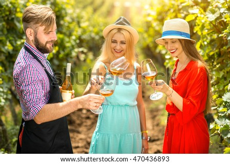 Handsome wine maker tasting wine with two women in colorful dresses on the vineyard. Wine degustation outdoors on the plantaion #470436893