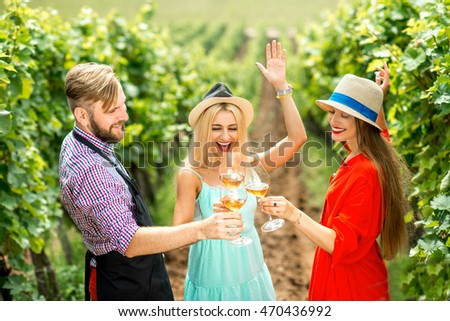Young women with handsome wine maker having fun clinking glasses on the vineyard #470436992
